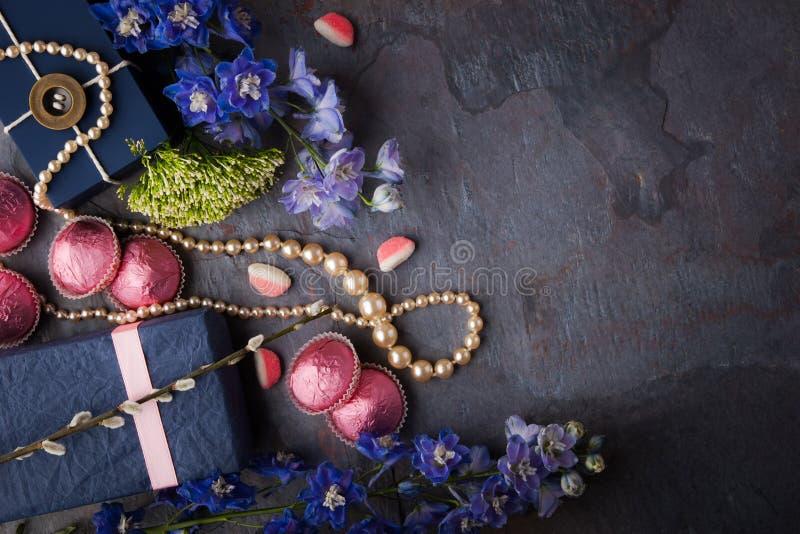 Fjädra gåvan med godisen, den pärlemorfärg halsbandet och blommor på en blå sto royaltyfri fotografi