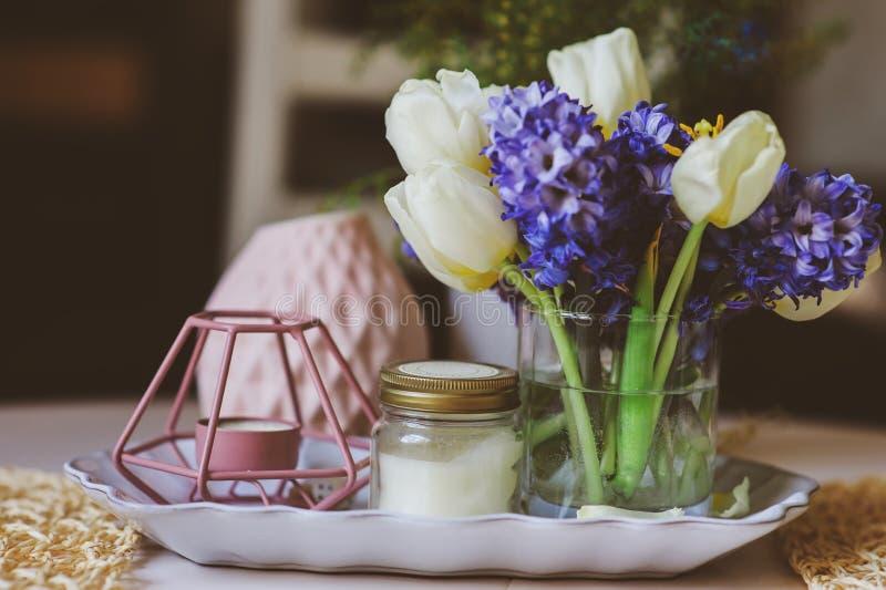 fjädra garneringar hemma på tabellen i modern scandinavian stil med blommor och aromatiska stearinljus royaltyfri foto