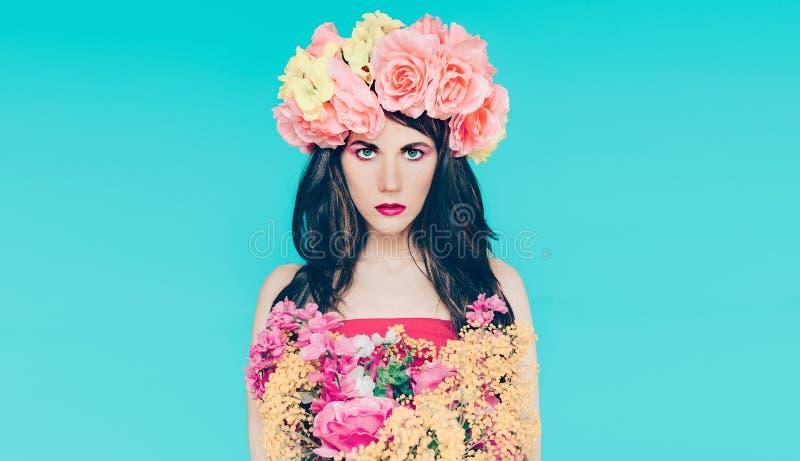 Fjädra modedamen med buketten av härliga blommor arkivfoton