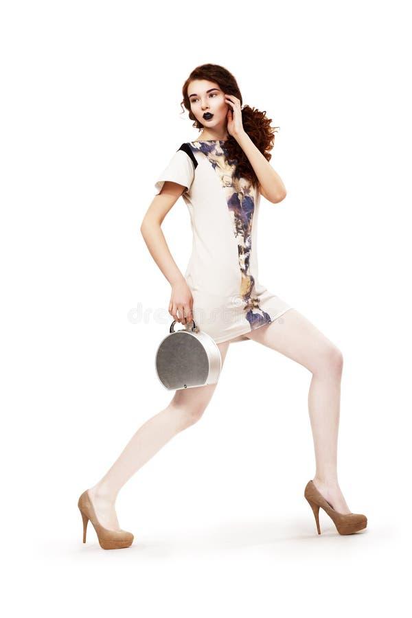 Fjädra samlingen. Dana kvinnan med handväskan ha på sig den moderna klänningen. Ferie arkivbilder