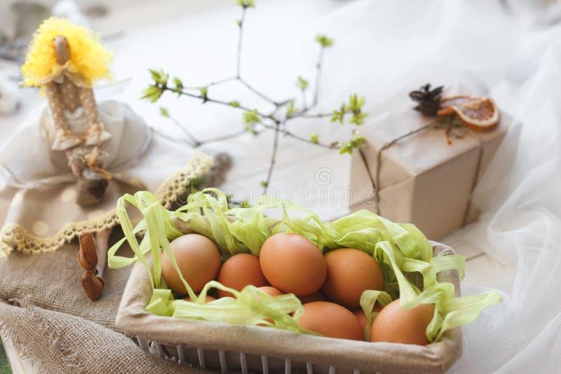 Fjädra sammansättning En leksakdocka, ägg i en korg och en festlig ask med en gåva royaltyfria bilder