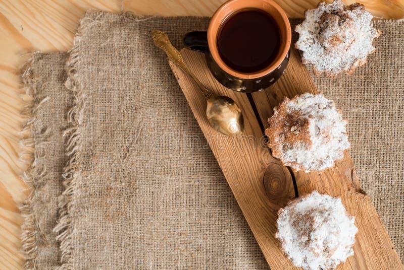 Fjädra sammansättningschokladmuffin med russin och varmt te i en lerakopp Sockerpulver på kakorna Söt frukost för morgon på arkivbilder