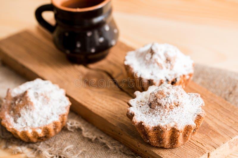 Fjädra sammansättningschokladmuffin med russin och varmt te i en lerakopp Sockerpulver på kakorna Söt frukost för morgon på royaltyfri bild