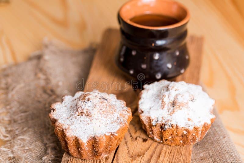 Fjädra sammansättningschokladmuffin med russin och varmt te i en lerakopp Sockerpulver på kakorna Söt frukost för morgon på fotografering för bildbyråer