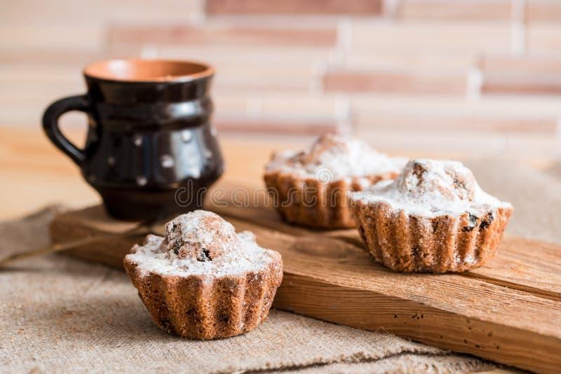 Fjädra sammansättningschokladmuffin med russin och varmt te i en lerakopp Sockerpulver på kakorna Söt frukost för morgon på arkivfoto