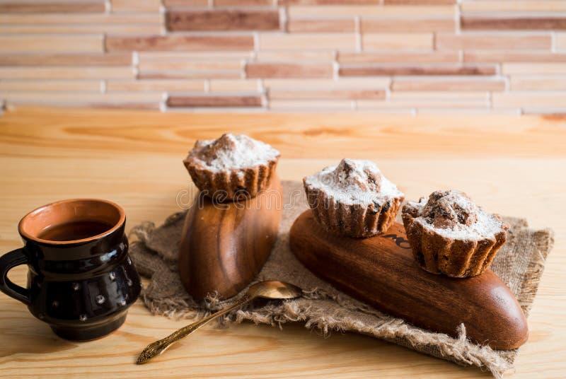 Fjädra sammansättningschokladmuffin med russin och varmt te i en lerakopp Sockerpulver på kakorna Söt frukost för morgon på arkivfoton