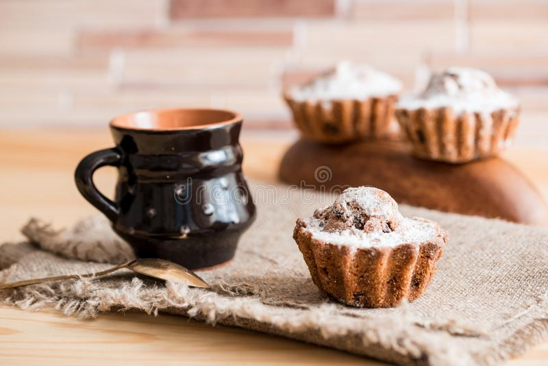 Fjädra sammansättningschokladmuffin med russin och varmt te i en lerakopp Sockerpulver på kakorna Söt frukost för morgon på royaltyfri foto