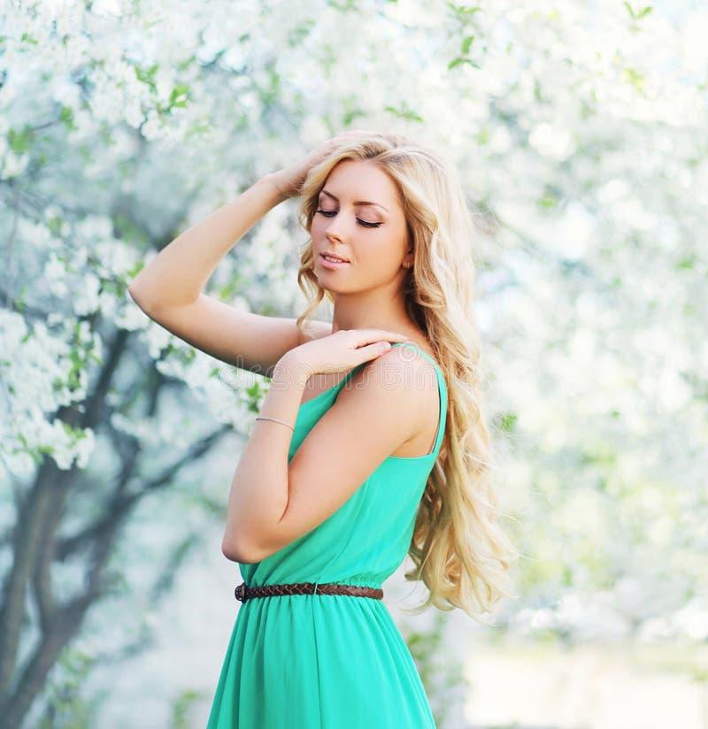 Fjädra ståenden av den älskvärda unga kvinnan som tycker om i en blomning royaltyfri fotografi