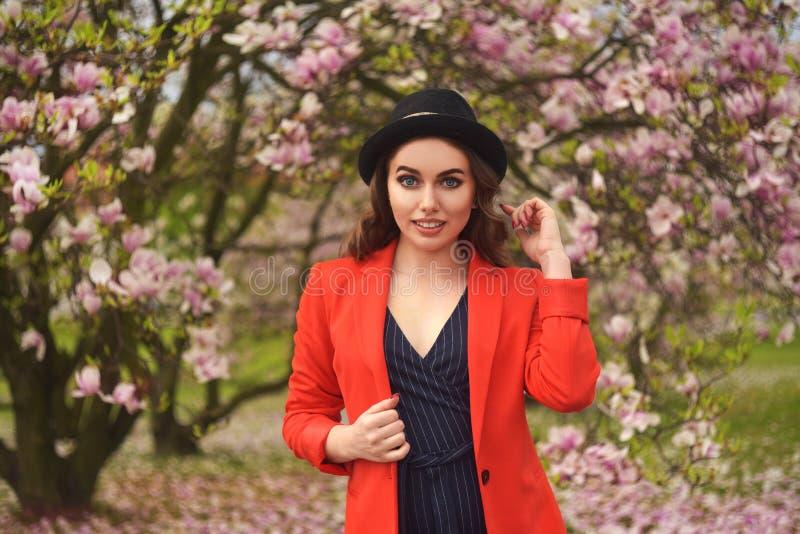 Fjädra ståenden för modeflickan utomhus i blommande träd Romantisk kvinna för skönhet i blommor Sinnlig dam som tycker om naturen royaltyfria bilder