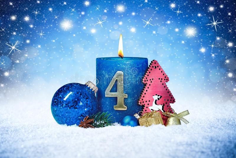 Fjärdedel söndag av den blåa stearinljuset för advent med röd garnering en för guld- metallnummer på träplankor i snöframdel av s arkivfoton