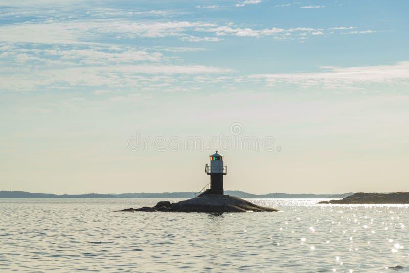 Fjärdhällan lighthouse sun haze Stockholm archipelago. Fjärdhällan lighthouse English: Bayskerry a fairway lighthouse at Jungfrufjärden bay in stock photo