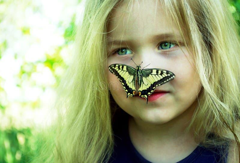 Fjäril som sitter på ett barn Barn med en fj?ril Fjärilsmachaon på lite flicka Selektivt fokusera Swallowtail fj?ril, royaltyfri fotografi