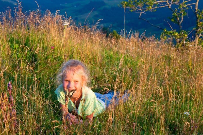 fjärilsflickan gräs berg arkivbilder
