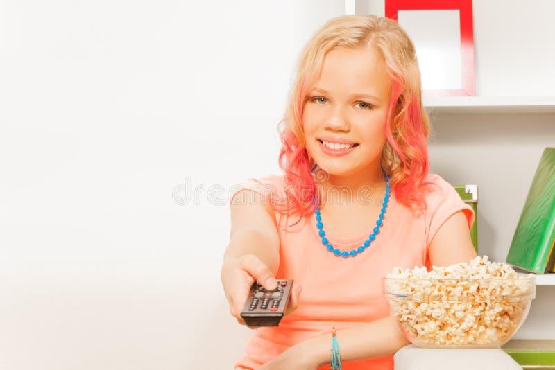 Fjärrkontroll och bunke för flicka hållande med popcorn arkivbilder