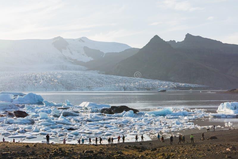 FJALLSARLON, ИСЛАНДИЯ - АВГУСТ 2018: люди идя на берег лагуны ледника Vatnajokull на заходе солнца стоковые изображения