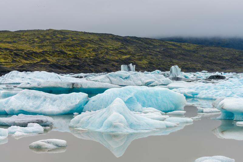 Fjallsarlon glacier lagoon at the end of Vatnajokull glacier. Green moss and volcanic ash in the background. Icelandic landscapes concept stock photo