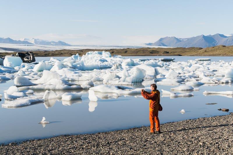 FJALLSARLON ISLAND - AUGUSTI 2018: Man i det orange omslaget som tar bilder av att sväva is i den Vatnajokull glaciärlagun royaltyfri fotografi
