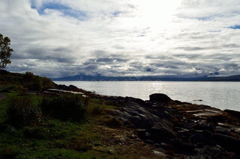 Fjord bleu, sunhine et nuages épais image stock