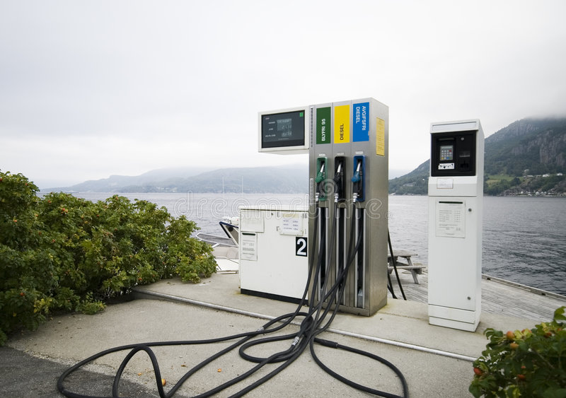 Fjord fuel. A single fuel distributor at a fjord, cloudy day, foggy mountains in the background stock images