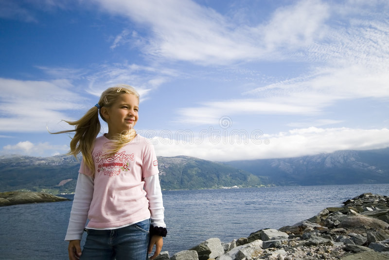 Fjord girl. A cute girl standing at a Norwegian fjord, looking at the side. Her hair in the air. MY KIDS COLLECTION stock photo