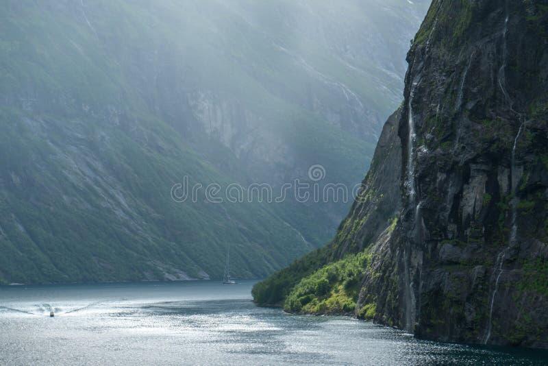 Fjord massif de geiranger en Norvège vue d'un bateau de croisière avec briller léger par les nuages et la cascade photos libres de droits