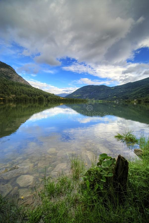 Fjord mirror. A fjord scenic, smooth surface mirroring the clouds and mountains stock photo