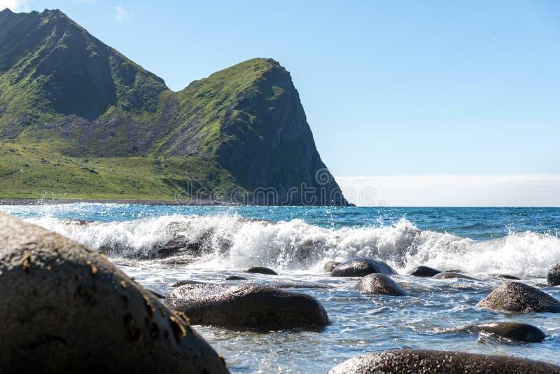 Fjorde Norwegens Lofoten - bewegt Spritzen auf Steinen auf der Ozeanküste wellenartig stockbild