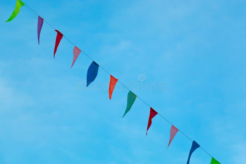 Flâmulas coloridas que penduram com corda contra o céu azul imagens de stock