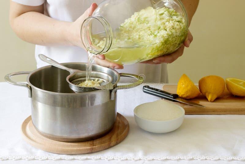 Fläderblommor, vatten, citron och socker, ingredienser och en kvinna som förbereder en fläderbärsirap Lantlig stil arkivbilder