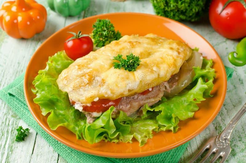 Fläskkotlett med tomater, potatisar och ost royaltyfria foton