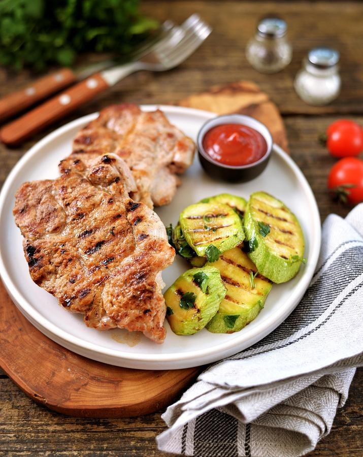 Fläskkotlett och grillad grönsak på träbakgrund arkivfoto