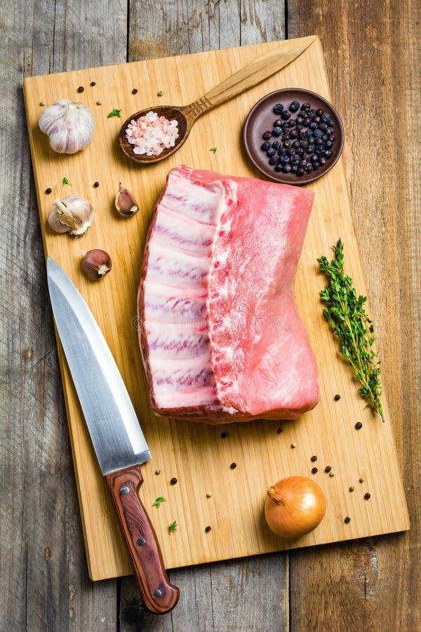 Fläskkotlett- och matlagningingredienser på träskärbräda royaltyfri fotografi