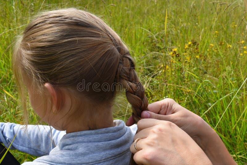 Flätade trådar för moder till dottern på hår i sommar royaltyfri fotografi