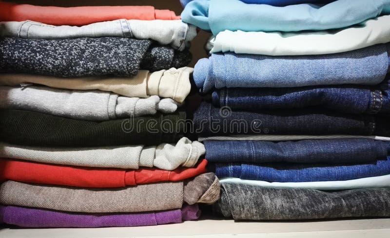 Flåsanden av olika färger som staplas i en garderob arkivfoton