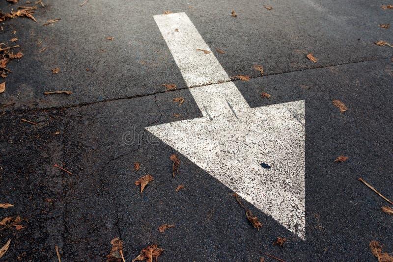Flèche blanche sur la route goudronnée, poteau de signalisation images libres de droits