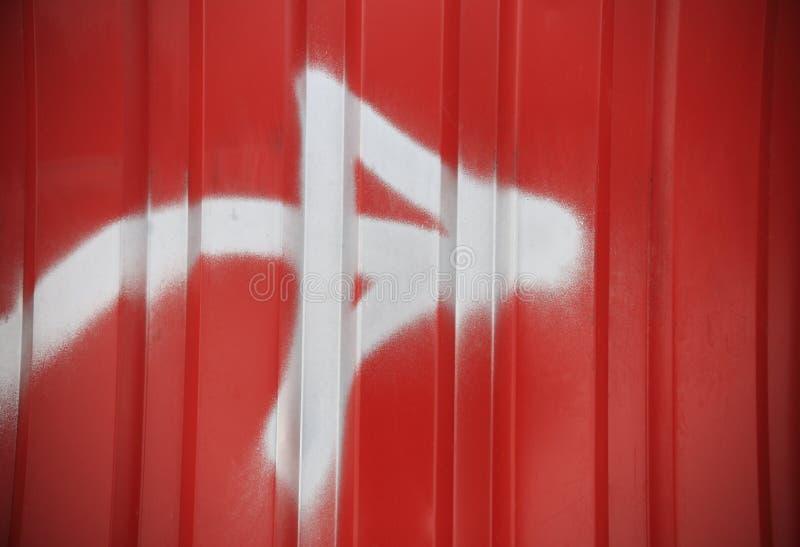 Flèche blanche sur le fond à nervures rouge de mur photographie stock libre de droits