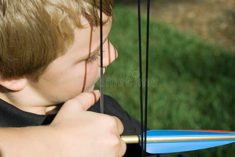 Flèche de tir de garçon/proche photo stock