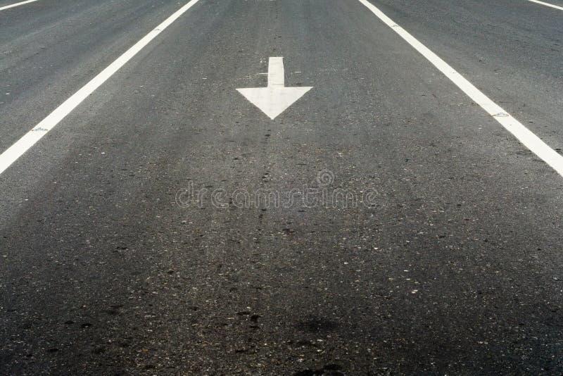Flèche et ligne blanches sur la route photographie stock
