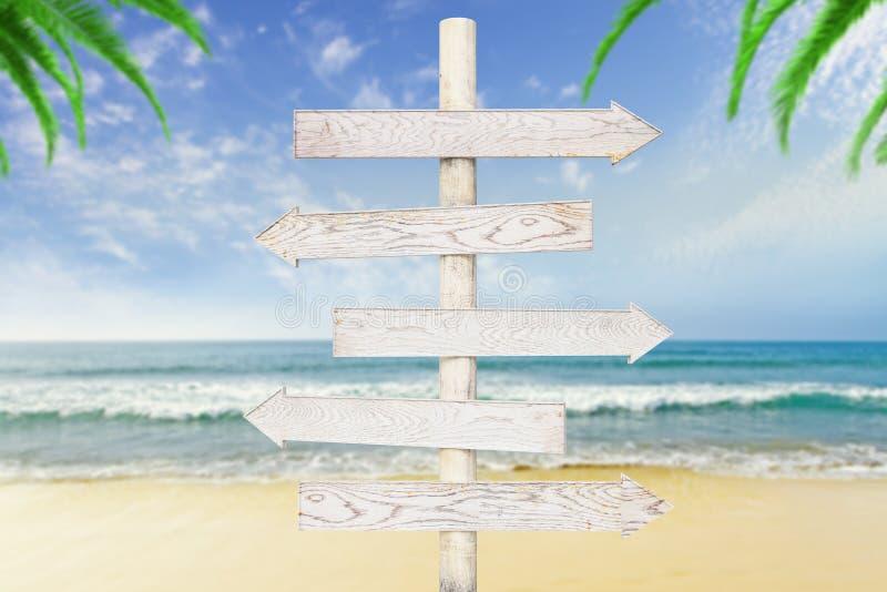 Flèche-indicateurs en bois blancs à l'océan image libre de droits