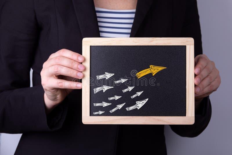 Flèche jaune comme chef de tendance avec beaucoup de flèches blanches comme disciple photographie stock libre de droits