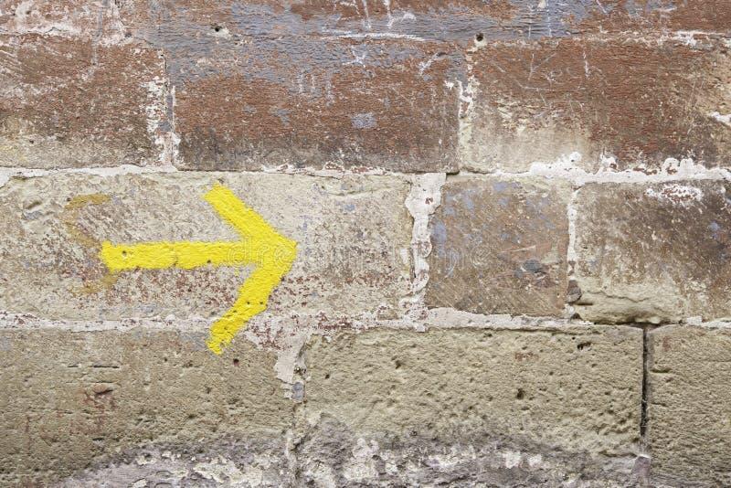 Flèche jaune sur un mur photo libre de droits