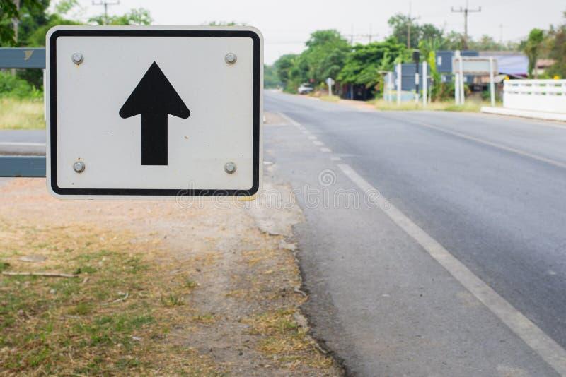 Flèche noire sur le poteau de signalisation blanc photos libres de droits