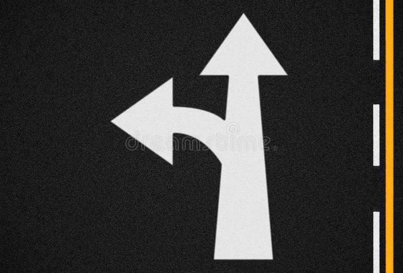 Flèche sur la texture de route goudronnée et les lignes du trafic images stock