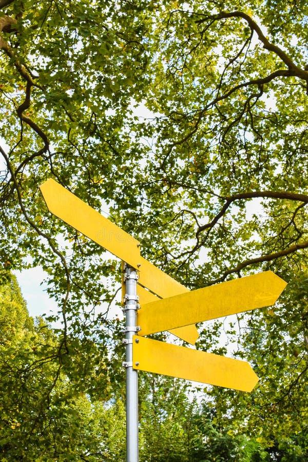 Flèches directionnelles vides jaunes sur le poteau indicateur images stock