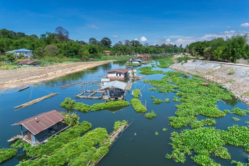 Flößen Sie Häuser und grünes eco sich hin- und herbewegende Bauernhöfe in einem Fluss lizenzfreies stockfoto