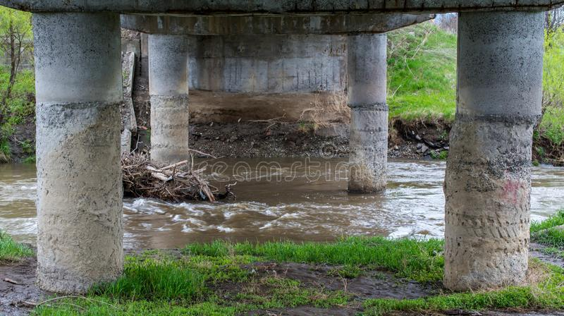 Flödande smutsig Olt flod under en konkret bro royaltyfri fotografi