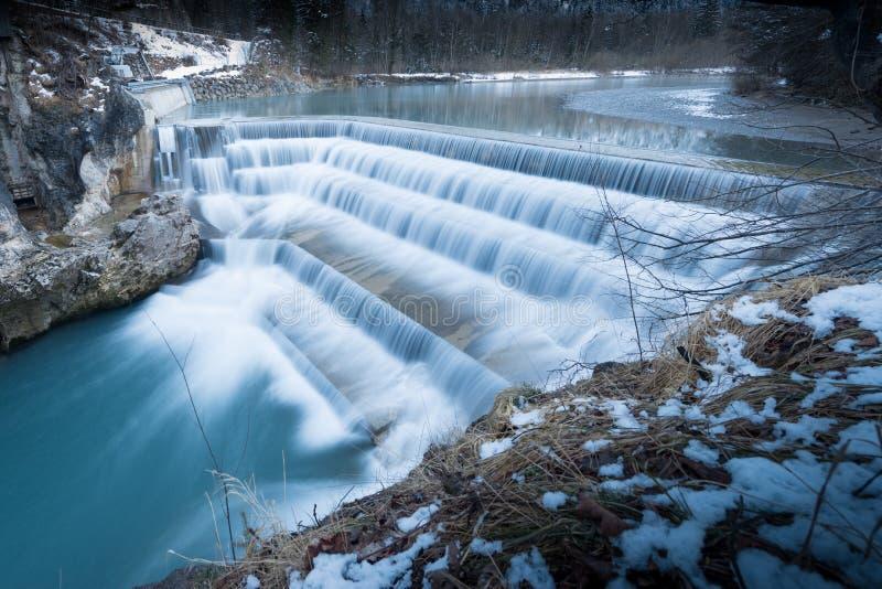 Flödande vatten över moment av floden faller på vintern arkivfoto