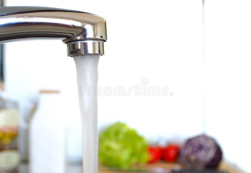 Flödande vatten i köket royaltyfria bilder