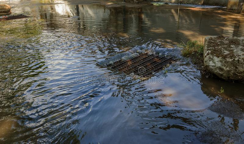 Flöde av vatten under hällregn och stoppa till av gatakloak Flödet av vatten under en stark orkan i storm förser med kloaker kloa arkivbild
