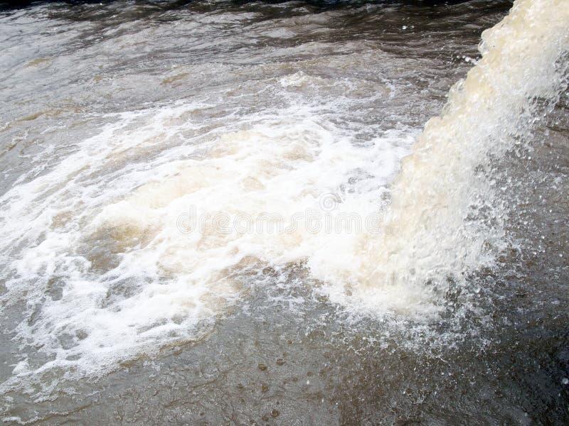 Flöde ut bevattnar från trumman av den industriella fabriken till floden arkivfoton